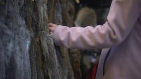 Junge Frau, die Pelzmäntel auf Straßenmesse, -einkaufen und -verbraucherschutzbewegung betrachtet stock footage