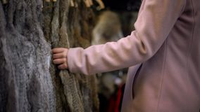 Junge Frau, die Pelzmäntel auf Straßenmarkt, -einkaufen und -verbraucherschutzbewegung betrachtet stockfoto