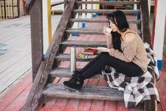 Junge Frau, die Picknick hat: trinkendes Tee- und Lesebuch Lizenzfreies Stockbild