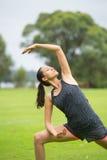 Junge Frau, die pilates im Park ausübt Stockbilder