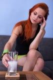 Junge Frau, die Pille für Kopfschmerzen vorbereitet Lizenzfreies Stockbild