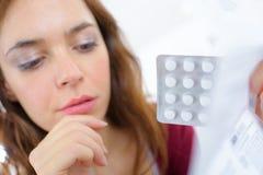 Junge Frau, die Pillen von der Blisterpackung einnimmt Stockbilder