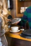 Junge Frau, die Pin In-Karte-Leser betritt stockfotografie