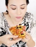 Junge Frau, die Pizza isst Stockbild