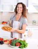 Junge Frau, die Pizza kocht Stockbild