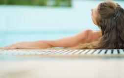 Junge Frau, die Pool genießt. hintere Ansicht Lizenzfreie Stockfotografie
