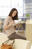 Junge Frau, die Post als Kommen von nach Hause überprüft Lizenzfreie Stockfotografie