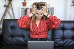 Junge Frau, die Probleme mit Laptop beim Sitzen auf einer Ledercouch hat stockbild