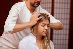 Junge Frau, die professionelle thailändische Massage genießt lizenzfreie stockfotografie