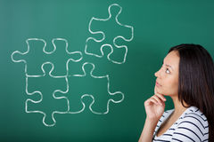 Junge Frau, die Puzzlespiel abschließt Lizenzfreie Stockfotografie
