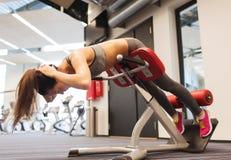 Junge Frau, die Rückenmuskulatur auf Bank in der Turnhalle biegt Lizenzfreie Stockfotografie