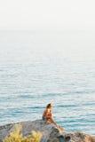 Junge Frau, die am Rand der Klippe sitzt stockfoto