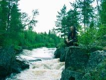 Junge Frau, die am Rand einer Klippe sitzt Stockfotografie