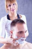 Junge Frau, die Rasierschaum auf männlichem Gesicht aufträgt stockfotos