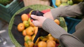 Junge Frau, die reife Mangos im Gemischtwarenladen wählt Null überschüssiges Mädchen des strengen Vegetariers kaufende Früchte un stock footage
