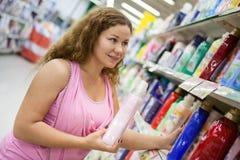 Junge Frau, die Reinigung reinigend im Shop hält stockfotos