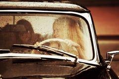 Junge Frau, die Retro- Auto im Regen fährt Lizenzfreie Stockfotos