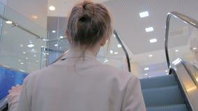 Junge Frau, die Rolltreppe weitergeht und herum im Mall schaut stock footage