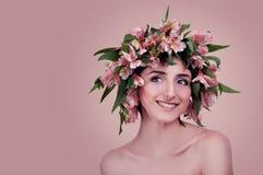 Junge Frau, die rosa Blumen auf ihrem Kopf trägt stockfoto