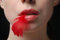 Junge Frau, die rote Feder anhält Stockfotos