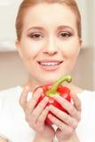 Junge Frau, die roten Pfeffer lächelt und hält lizenzfreies stockfoto