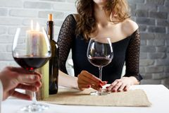 Junge Frau, die Rotwein auf einem Datum in einem Restaurant trinkt lizenzfreie stockfotos