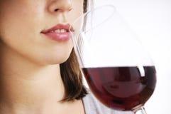 Junge Frau, die Rotwein trinkt Stockbilder