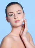 Junge Frau, die Sahne auf Gesicht aufträgt Stockbild