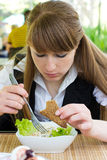 Junge Frau, die Salat isst Stockfoto