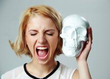 Junge Frau, die Schädel schreit und hält Stockbild