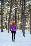 Junge Frau, die in schönen Winter-Wald bei Sunny Frosty Day läuft Aktives Lebensstilkonzept lizenzfreie stockfotos
