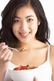 Junge Frau, die Schüssel Getreide im Studio isst lizenzfreie stockfotos