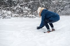 Junge Frau, die Schneeball draußen an einem schneebedeckten Tag macht lizenzfreie stockfotos