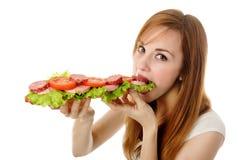 Junge Frau, die Schnellimbiß isst Stockfotos