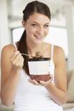 Junge Frau, die Schokoladen-Eiscreme isst Stockfoto