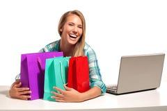 Junge Frau, die am Schreibtisch online kauft sitzt Lizenzfreie Stockfotos