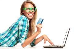 Junge Frau, die am Schreibtisch online kauft sitzt Lizenzfreies Stockfoto