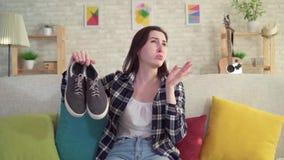 Junge Frau, die Schuhe in ihren Händen und unangenehm riechen hält stock video footage
