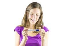 Junge Frau, die Schwangerschaftstest betrachtet lizenzfreie stockfotos