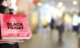 Junge Frau, die schwarze Freitag-Einkaufstasche hält Lizenzfreie Stockfotos