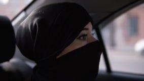 Junge Frau, die schwarzes niqab trägt Folowing die Regelfrau trägt das niqab während ihre Straße im Auto und sitzt auf stock footage