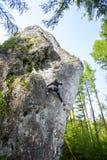 Junge Frau, die schwierigen Felsen im Wald klettert Stockfotos