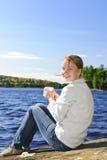 Junge Frau, die am Seeufer sich entspannt Stockfoto