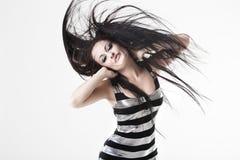 Junge Frau, die sehr langes dunkles Haar schlägt Lizenzfreie Stockfotos