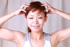 Junge Frau, die Selbstkopfmassage tut Stockfotografie