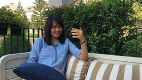 Junge Frau, die Selbstporträt unter Verwendung des Smartphone macht Mädchen, das selfie macht stock footage