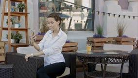 Junge Frau, die Selbstporträt unter Verwendung des Smartphone macht Mädchen, das selfie macht Frau im Café Frau allein Selbstport stock footage