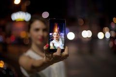 Junge Frau, die selfie in der Stadt nimmt Stockfotos