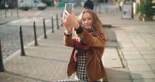 Junge Frau, die selfie mit Handy in der sonnigen Stadtstraße nimmt Stockbilder