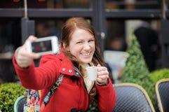 Junge Frau, die selfie mit intelligentem Telefon in einem Straßencafé nimmt Lizenzfreie Stockbilder